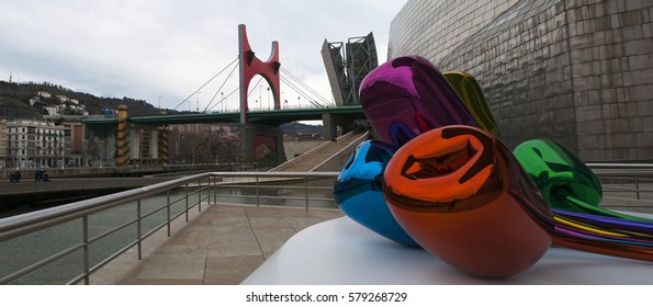 Spain, 27/01/2017: the Tulips, a bouquet of multicolor balloon flowers sculpture made by the artist Jeff Koons and located at the exterior of the Guggenheim Museum Bilbao, with view of the skyline