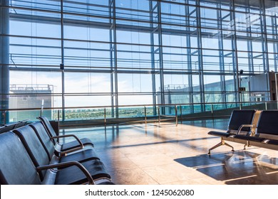 SPAIN, ALICANTE - NOVEMBER 27, 2018 Airport lounge waiting area with no people. Rows of chairs big windows view onto landing field. Sunlight streaming through glass wall. Conceptual atmospheric image