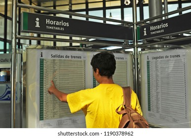 Cádiz, Spain - Aug 25, 2012: A boy looking at the departure and arrival timetable of the trains (Horario salida y llegada de trenes) in the railway station. Cadiz, Andalusia, Spain