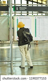 Cádiz, Spain - Aug 25, 2012: Woman looking at the arrival timetable of the trains (Horario llegada de trenes) at the railway station. Cadiz, Andalusia, Spain