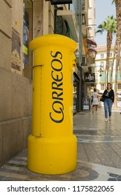 MÁLAGA, SPAIN, AUGUST 28, 2018: Big yellow mailbox at the historic center of Málaga, Spain, with people walking in the background