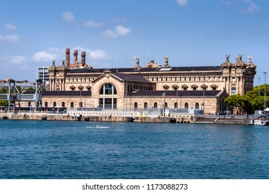 Spain, Barcelona: Big building with taxation office (Agencia Tributaria) between Mirador de Colum and Placa de les Drassanes in the city center of Spanish town with ocean and blue sky. July 01, 2018