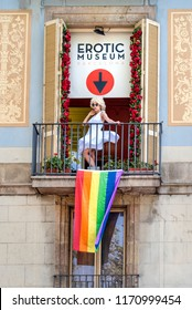 Spain, Barcelona: Marilyn Monroe lookalike in white dress on balcony with rainbow flag of the public erotic museum at famous boulevard La Rambla in city center of the Spanish town. July 01, 2018