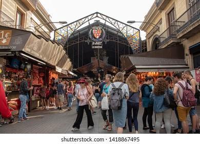 Spain, Barcelona - May 2018: tourists walk past La Bogueria, food market off La Rambla in Barcelona