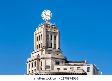 Spain, Barcelona: Roof top and round clock of big neoclassical building at the famous Catalonia Square (Placa de Catalunya) in the city center of the Spanish town with blue sky. July 01, 2018