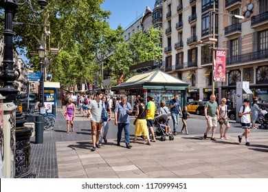 Spain, Barcelona: Street scene with people residents tourists women men children on famous boulevard La Rambla in the city center of the Spanish town, kiosk, green trees and cars. July 01, 2018