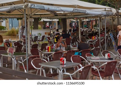 SPAIN, Calella - SEPTEMBER 15, 2016: Street cafe under umbrellas in Calella, Spain.