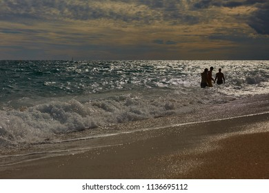 SPAIN, Calella - SEPTEMBER 15, 2016: People enjoy the sea waves and landscape in cloudy weather in Calella, Spain.