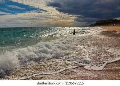 SPAIN, Calella - SEPTEMBER 15, 2016: A man stands on the seashore in cloudy weather in Calella, Spain.