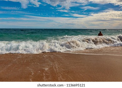 SPAIN, Calella - SEPTEMBER 15, 2016: A man stands on the waves in a bright sunny day in Calella, Spain.