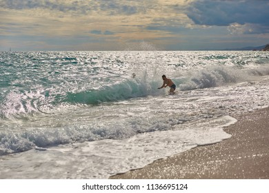 SPAIN, Calella - SEPTEMBER 15, 2016: Man catches the sea wave with a cloudy summer day in Calella, Spain.