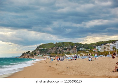 SPAIN, Calella - SEPTEMBER 15, 2016: People on a sea beach in cloudy weather in Calella, Spain.
