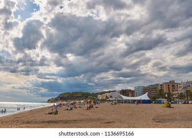 SPAIN, Calella - SEPTEMBER 15, 2016: People rest on the beach in a cloudy weather in Calella, Spain.