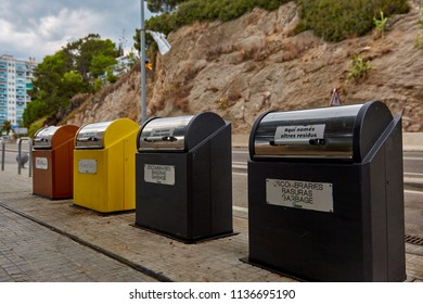 SPAIN, Calella - SEPTEMBER 15, 2016: Yellow, red and black garbage cans for sorting waste near the roadway to Calella, Spain.