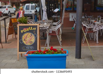 SPAIN, Calella - SEPTEMBER 15, 2016: A cozy open cafe in Calella, Spain, where they sell a national dish - paella.