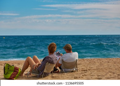 SPAIN, Calella - SEPTEMBER 15, 2016: A man and a woman are sitting on deckchairs on the beach in bright sunny weather in Calella, Spain.