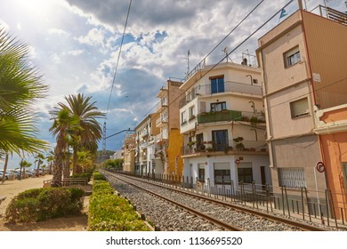 SPAIN, Calella - SEPTEMBER 15, 2016: A multi-storey house near the railway rails and palm avenue in Calella, Spain.
