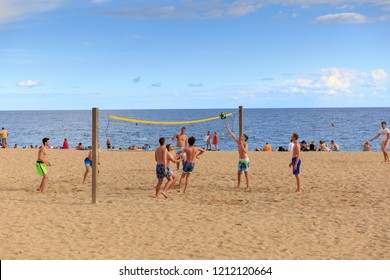 SPAIN, Calella - SEPTEMBER 15, 2016: Teams of men playing volleyball on the beach on a bright sunny day in Calella, Spain.