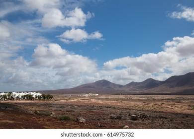 Spain Canary Islands Lanzarote landscape. Sand, black rocks, volcanos