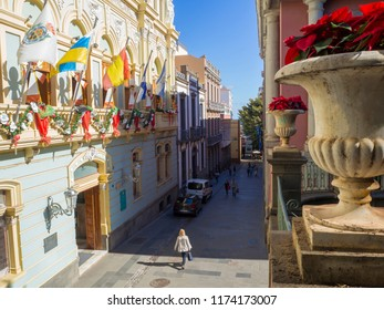 Spain, Canary islands, Santa Cruz de Tenerife, December 27, 2017: view on street in city center with christmas decoration, coloful garland and christmas star in flower pot