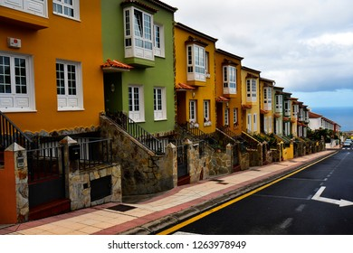 Spain, Canary Islands, Tenerife, colorful terraced houses in street that all look similar in the mountain village La Orotava with Atlantic ocean in background