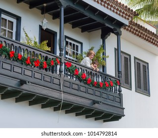 Spain, Canary Islands, Tenerife, Icod de Vinos, 2017, December 19: Grandmather and her baby girl looking out from wooden balcony decorated by christmas star wreath, typical traditional canary house