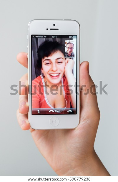 SPAIN - DECEMBER 10, 2013: Young woman talking via FaceTime on Apple iPhone