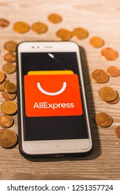 León, Spain - December 6, 2018:  aliexpress app in the screen of a mobile phone with a wood background