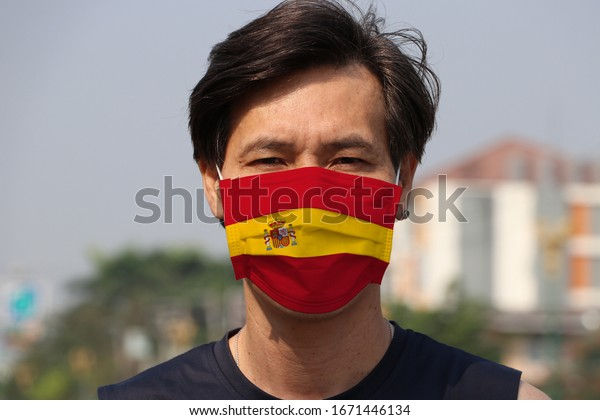 Spain flag on hygienic mask. Masked Asian man prevent germs. concept of Tiny Particle protection or virus corona or Covid19.