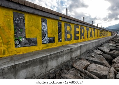Spain, Girona, 26, December, 2018, Freedom and Republic.  Political stencil message created with yellow paint over a graffiti covered wall  looking over the Mediterranean Sea.