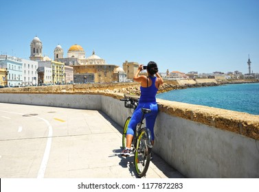 Cádiz, Spain - Jun 20, 2015: Woman on bike taking a picture of the Cathedral, bike path in Cádiz, Andalusia, Spain