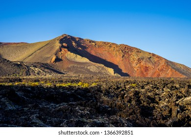 Spain, Lanzarote, Colorful red volcanic crater surrounded by lava in timanfaya volcanic nature landscape