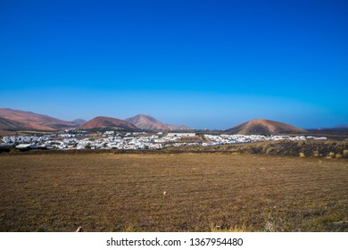 Spain, Lanzarote, Little village ye between majestic volcano mountains and black lava fields