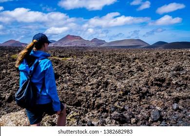 Spain, Lanzarote, Young woman enjoying stunning caldera lava and volcanoe landscape