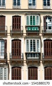 Spain – Malaga city:  A down town, turn of the century residential building. Elegant, symmetrical design making simple windows and balconies, a balanced piece of art.