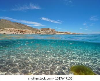 Spain Mediterranean coast with a castle and school of fish (bogue) with sand underwater sea, el Playazo de Rodalquilar, Almeria, Andalusia, split view half over and under water