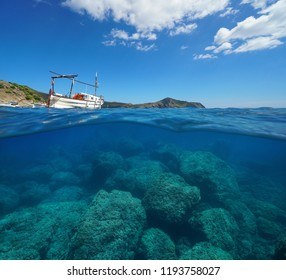Spain Mediterranean sea a typical boat with the coastline in background and rocks underwater, split view above and below water surface, Costa Brava, Roses, Catalonia, Girona