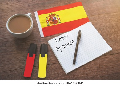 spain national flag, cup of coffee, notebook with the inscription learn spanish, two markers on the desktop, foreign language learning concept