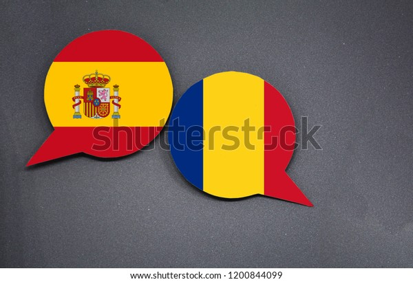 Spain and Romania flags with two speech bubbles on dark gray background