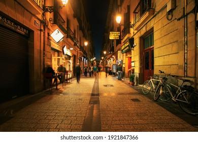 Spain - San-Sebastian - October 27-2017 : San Sebastian typical small street view with lively tapas bars and restaurants at night