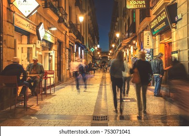 SPAIN SAN-SEBASTIAN - OCTOBER 27.2017 : Selective focus on buildings with abstract people motion walking on typical small street and lively tapas bars and restaurants at night