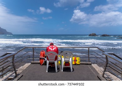 SPAIN, TENERIFE - 01 JULY 2017. The water rescuer at the post, on the observation deck, watches the sea, Taganana, Canary Islands. Accident prevention and water rescue. Duty holding orange float.