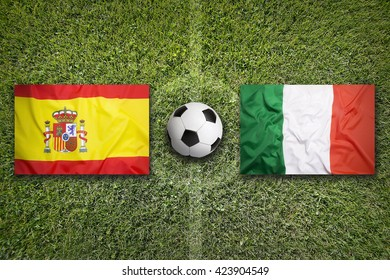 Spain vs. Italy flags on a green soccer field