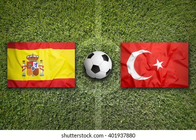 Spain vs. Turkey flags on green soccer field