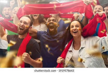 Spainian football, soccer fans cheering their team with a red scarfs at stadium. Excited fans cheering a goal, supporting favourite players. Concept of sport, human emotions, entertainment. - Shutterstock ID 1919578643