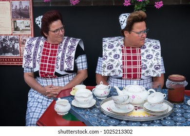 Spakenburg, Utrecht, The Netherlands - September 5, 2017 : Two ladies in traditional dress of Spakenburg on the yearly fishermen's day in September with an old vintage tea set.