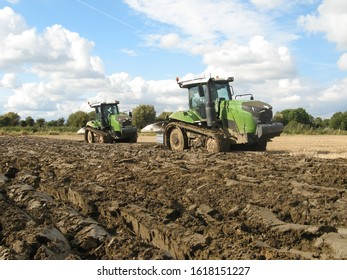 Spalding, England - okt 7,2019:  two big tractors with caterpillar tracks are plowing the fiels in autumn with a blue cloudy sky in the background