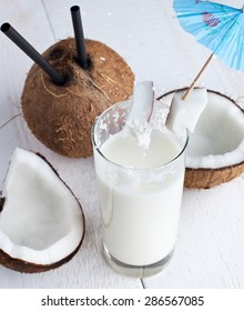 Spalsh drink with milk and coconut on white wooden table.