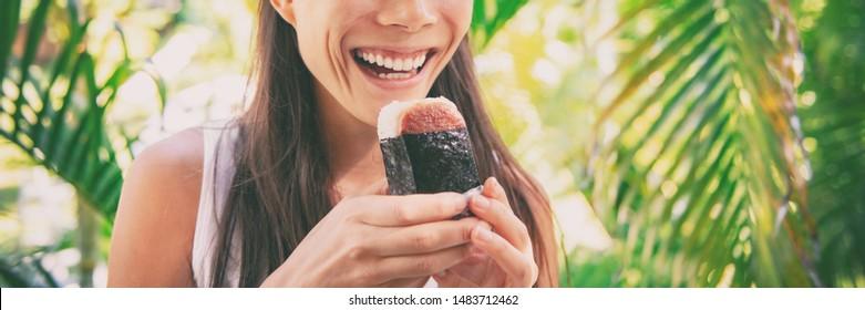 Spam musubi rice ball hawaiian food banner panorama. Woman tourist eating japanese snack local food of Hawaii panoramic background.