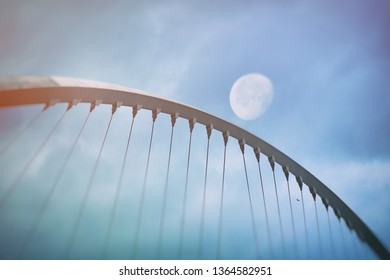 Span of a bridge with the moon in background. Arty with blue colors